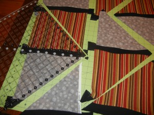 Cut out large triangles with like fabrics on opposite 'sides' of the triangle.