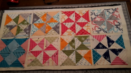 The charm pack made eight potholders.  Onto a large piece of backing, I placed one layer of Insul-bright and one layer of 100% cotton batting.  Pinned all of the potholders down and then straight-line quilted with a walking foot.